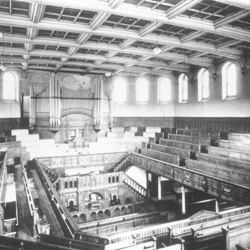 A black-and-white photograph of the theatre when it was a mission. At the rear there is a large organ and there are pews/benches around the four corners of the building.