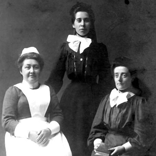 A photograph of three women who lived at the mission. One is wearing a nurse-like uniform, the other are in all black with white bows.