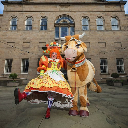 A photograph of a pantomime dame and cow in front of the theatre.
