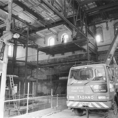 A photograph of the main auditorium during construction in the early 1990s. There is a large crane and a number of builders wearing hard hats around the construction site.