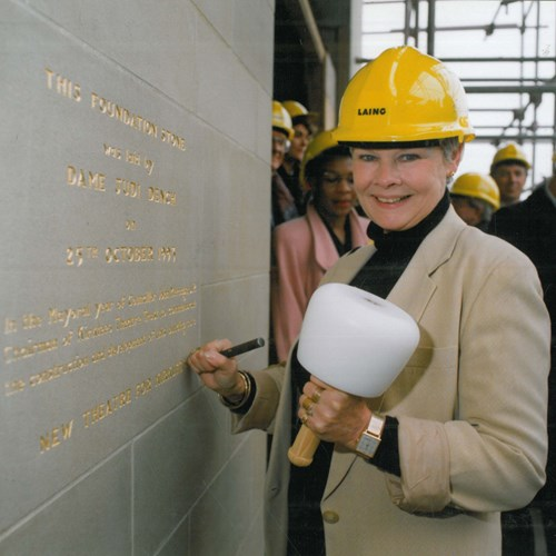 A photograph of actress Dame Judi Dench wearing a hard hat and holding a large mallet, laying the ornamental foundation stone of the building in 1994.